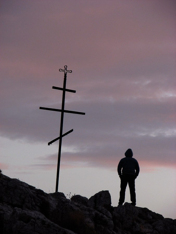 Silhouette of a young man standing next to a cross on sunset